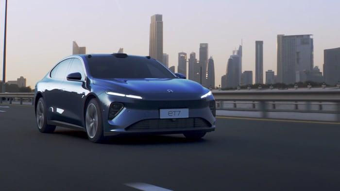 Nio ET7 luxury electric sedan in front of city skyline.