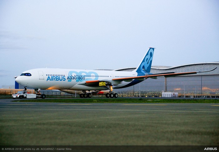 An Airbus A330neo parked in front of an aircraft hangar.