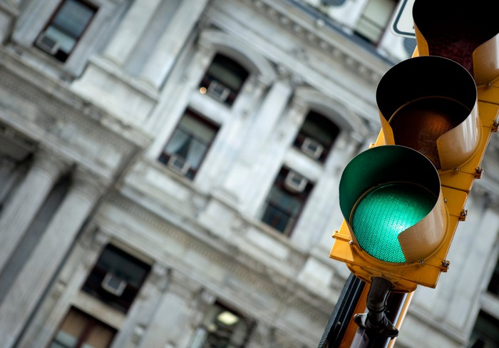 Traffic light in an urban environment showing green.