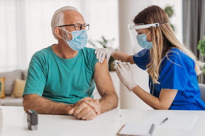 A clinician in mask and shield administering a COVID vaccine to a man wearing a mask.