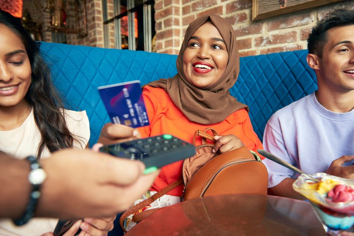 A woman wearing a hijab sitting with a man and a woman at a restaurant and paying with a credit card/