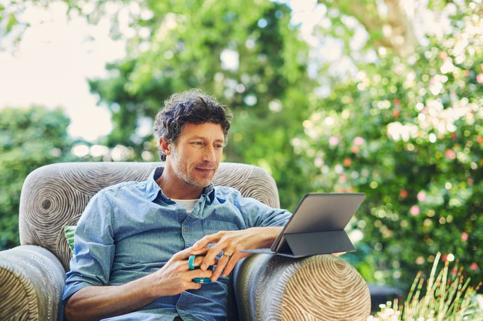 Man sitting in chair outdoors looking at tablet