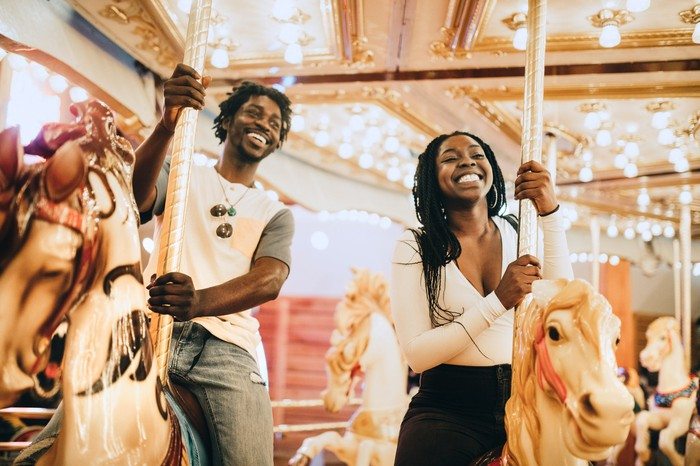 Two adults smiling on a theme park carousel.