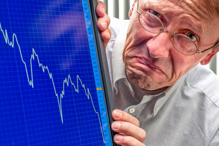 A frowning person next to a stock chart on a computer screen depicting a market crash.