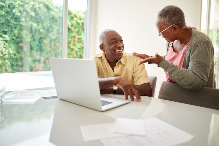 Happy couple reviewing retirement investments on a laptop.