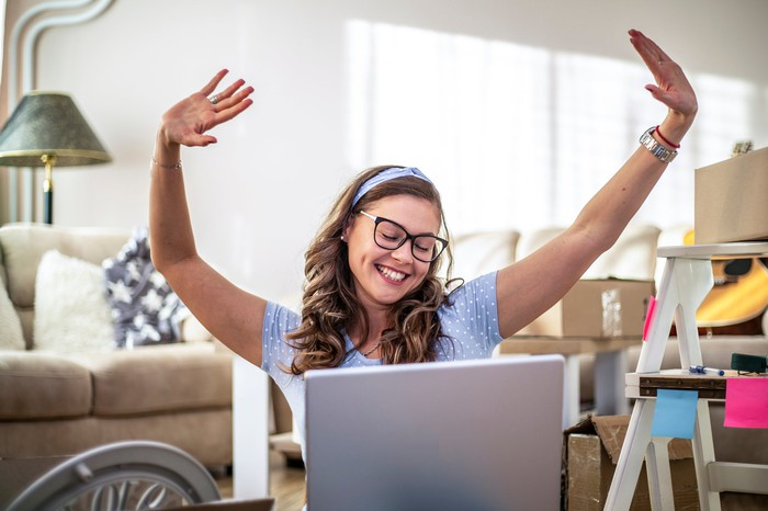 A happy person holds their arms in the air while looking at a laptop.