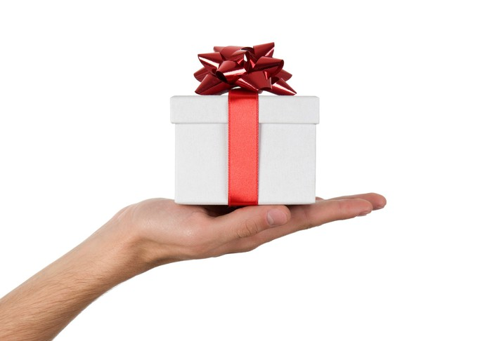 An outstretched hand holding a white box with a red bow tied around it.
