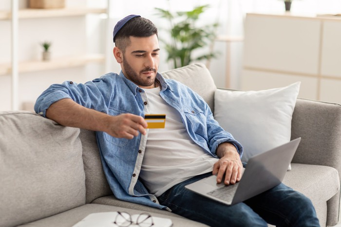 A man sitting on a couch with  computer and holding a credit card.