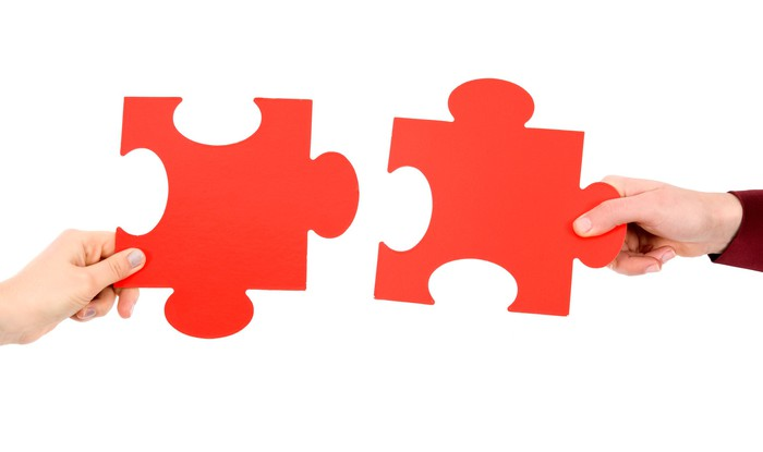 Two hands putting red puzzle pieces together.
