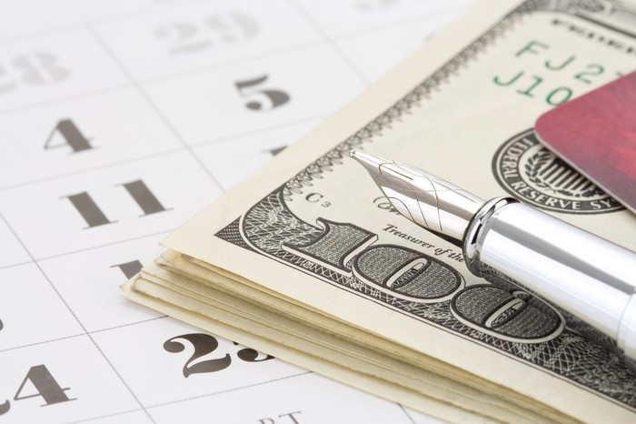 A stack of hundred-dollar bills resting on a calendar, next to a fountain pen and a credit card.