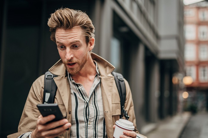 Young person on city street looking with surprise at their smartphone.