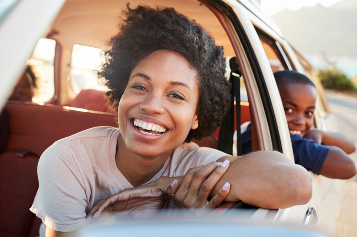 A smiling mother leaning out the window of a parked car, with her children in the back seat.