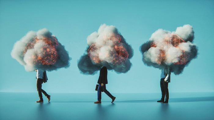"""Three people with their heads engulfed by """"digital"""" clouds."""