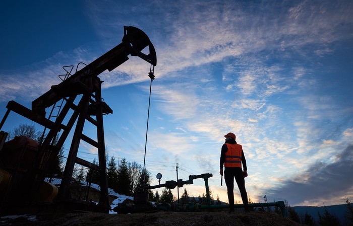 The silhouette of a person next to an oil well.
