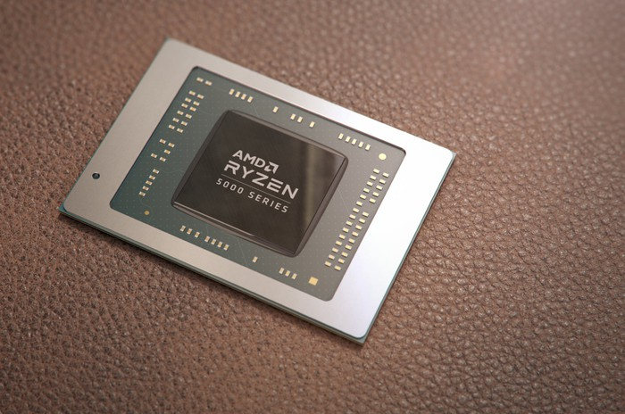 The AMD Ryzen 5000 processor chip appears on a paved surface