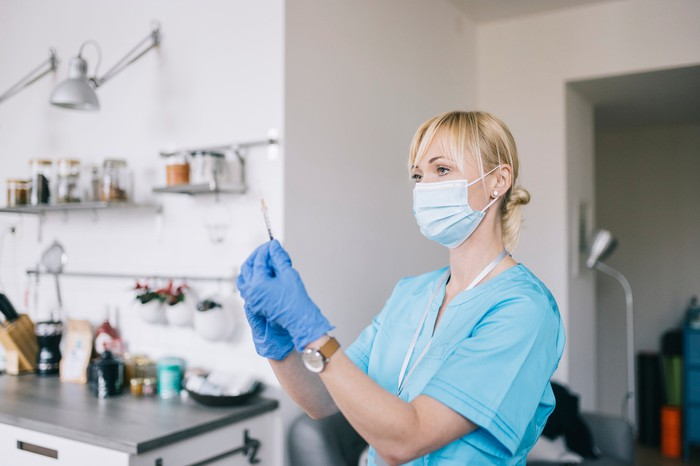 A person wearing scrubs holds a syringe while standing in a kitchen.