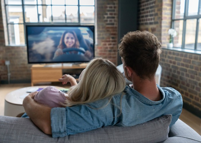 Two people cuddling on a couch watching TV.