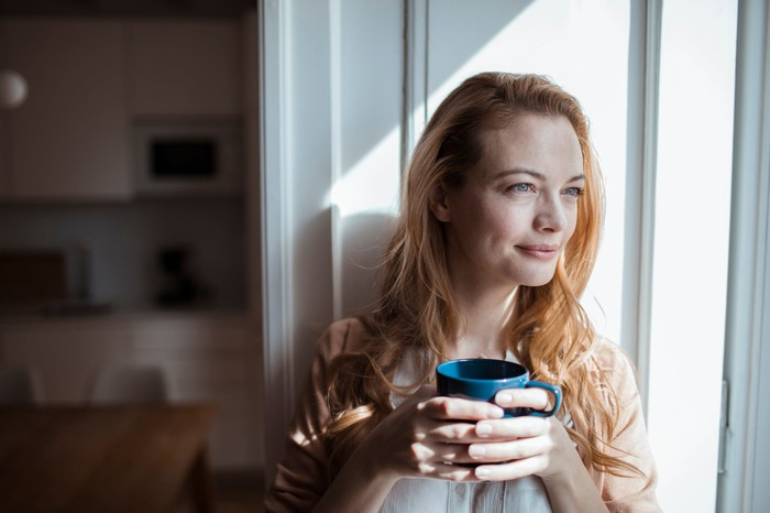 Smiling person holding coffee mug sitting in window and looking outside
