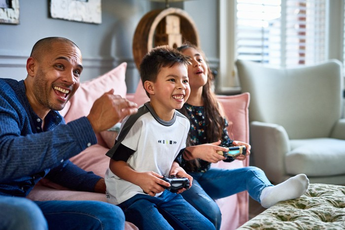 Two kids holding video game controllers with an adult on a couch.