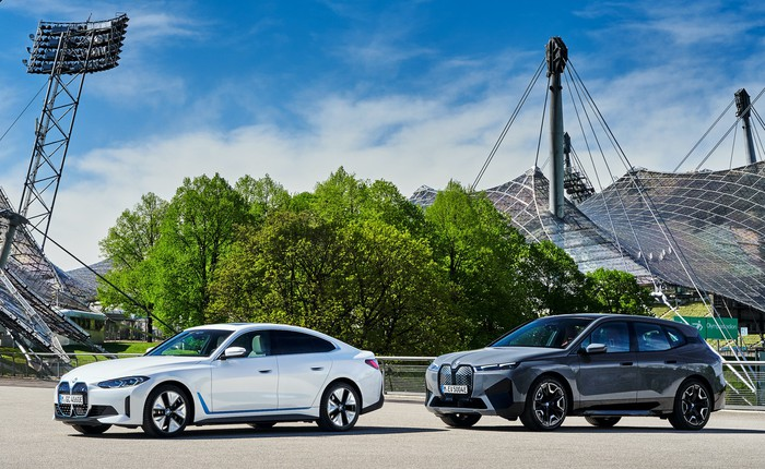 A white BMW i4, an electric sedan, and a silver BMW iX, an electric SUV, parked on the company's headquarters campus in Germany.