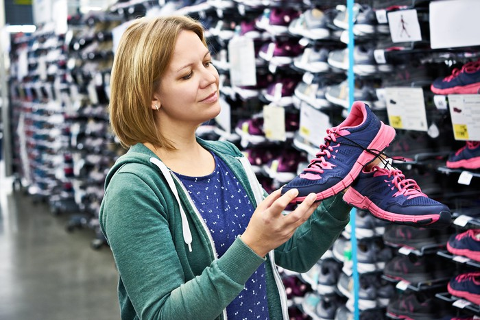 A person looking at shoes in a store.