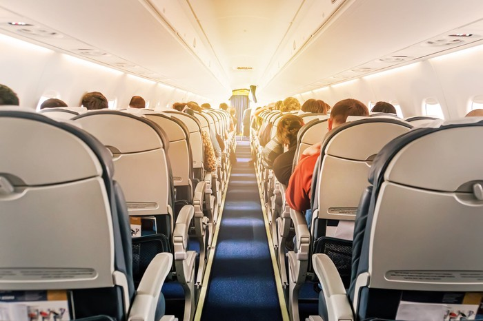 Airplane passengers seated inside of a commercial aircraft.