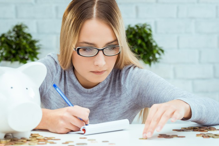 A person writing in a notebook while counting pennies from a piggybank.