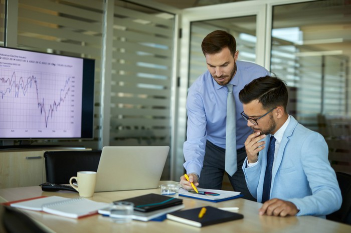 Two workers analyze a financial chart in an office.