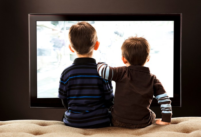 The backs of two boys sitting on a couch and watching television.