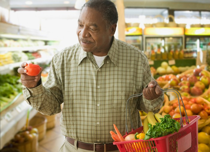Someone in a grocery store looking at the tomato in his hand while holding a basket of produce in his other hand.