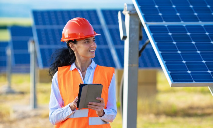 Wearing a hard hat and standing next to rows of solar panels a woman works on a tablet.