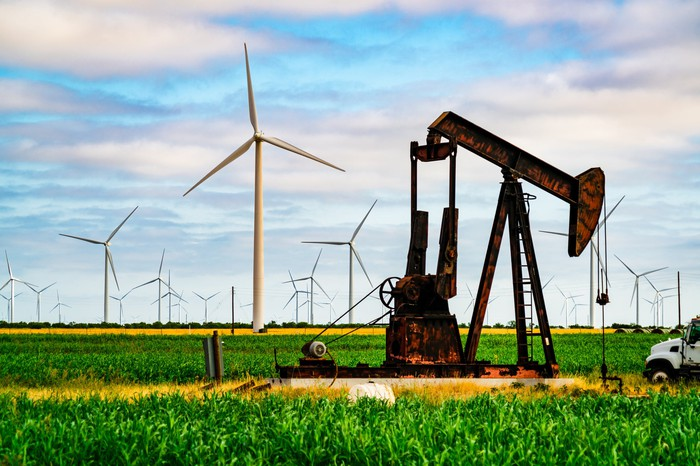 Oil pumpjack in a field with wind turbines in the distance.