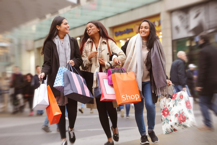 Three women holding shopping bags and walking through a mall.