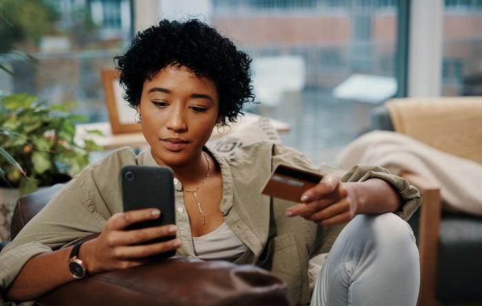 Un acheteur saisit des informations de carte de crédit dans un smartphone.