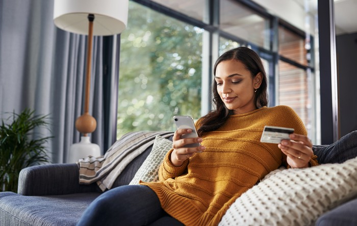 Person sitting on a couch holding a credit card in one hand and a smartphone in the other.