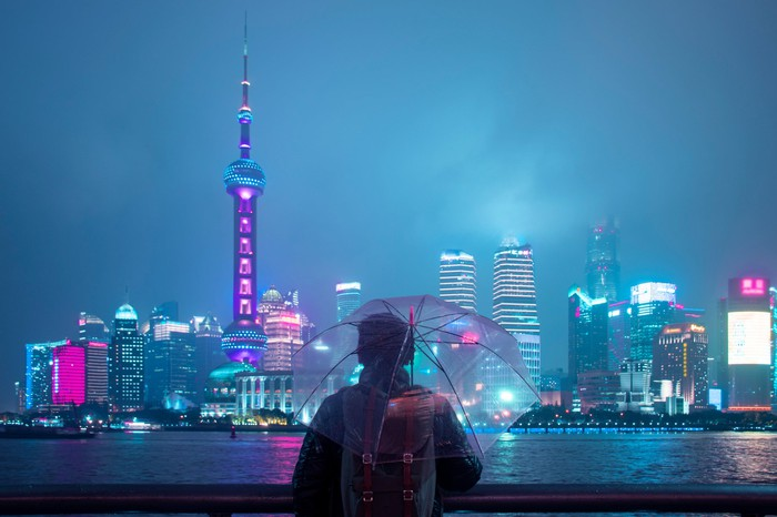 A person holding an umbrella in front of the city of Shanghai at night.