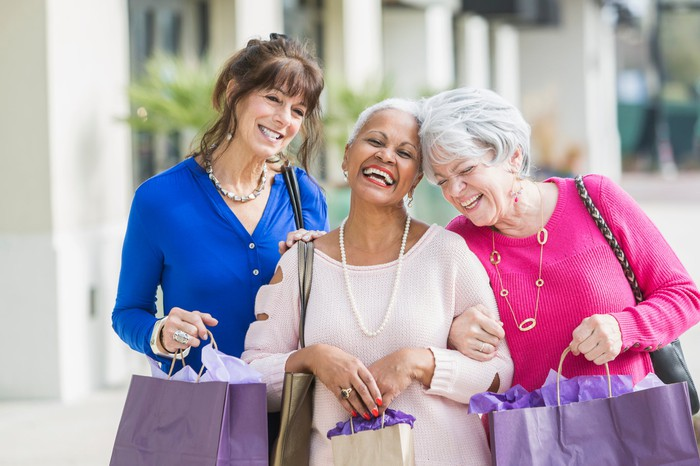Three smiling people holding shopping bags.