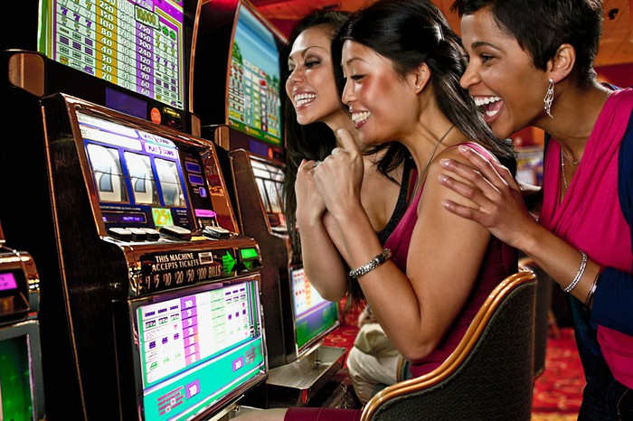 People sitting at a slot machine in a casino excited about the outcome of a spin.