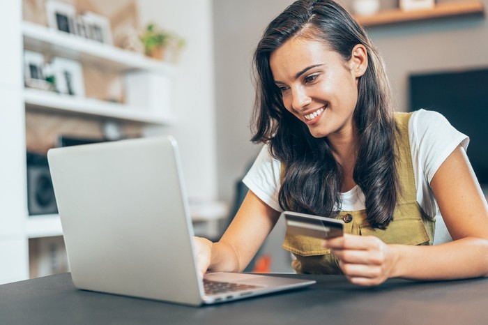 Young person making an online purchase through her laptop with a credit card.