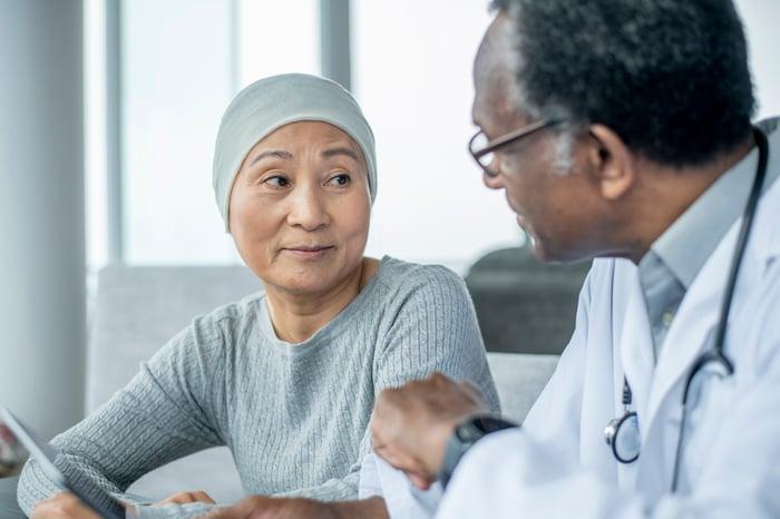 Professionnel de la santé parlant à un patient portant une casquette anti-chute.
