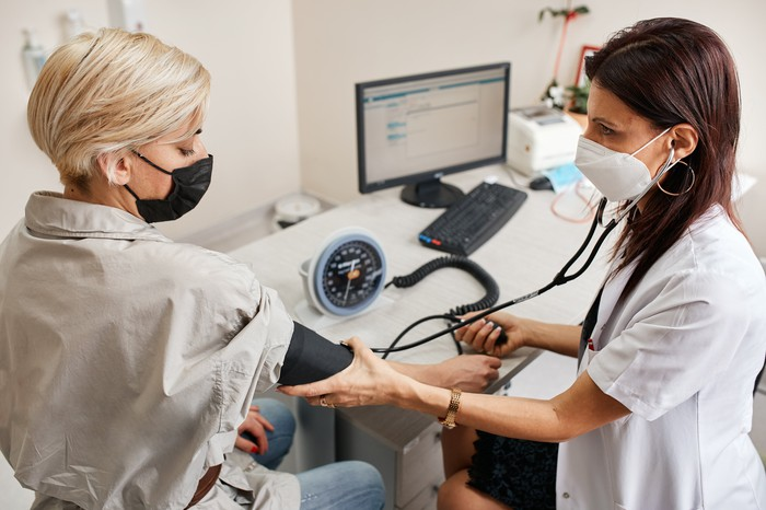A healthcare worker takes a patient's blood pressure.