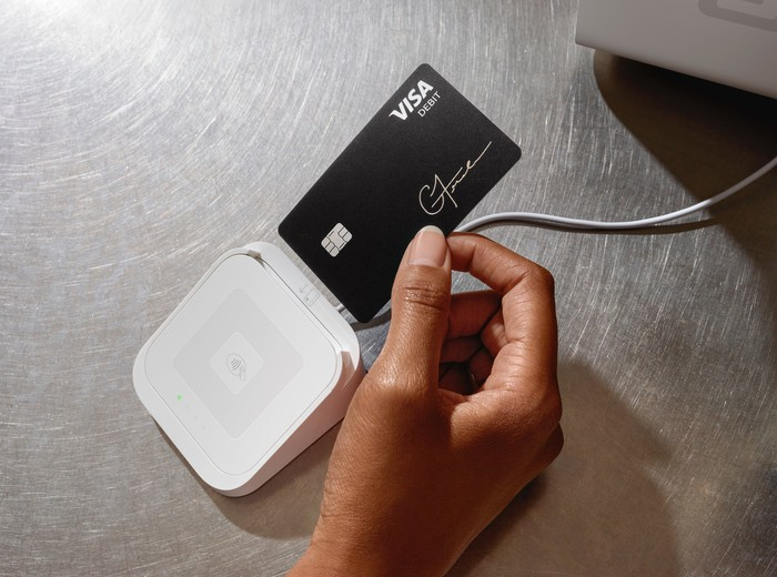 Hand poised to insert a black debit card into a white Square card reader.
