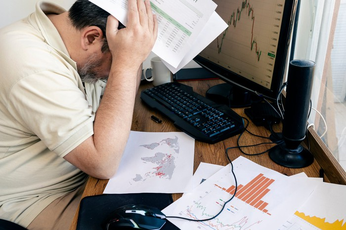 A person sits with their head in their hands at a desk with financial charts scattered on it.