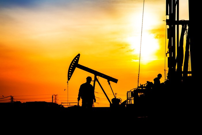 Workers on an oil field at sunset.