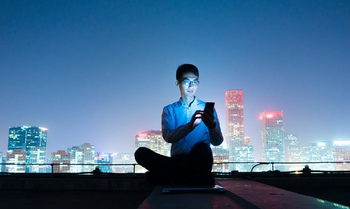 A young man operates his cell phone sitting on a rooftop at night in front of a skyline.