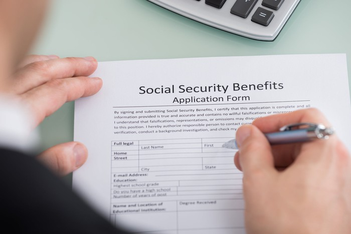 Person filling out Social Security benefits application form.