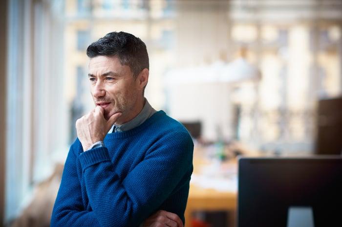 Une personne qui regarde par la fenêtre en réfléchissant à une décision.