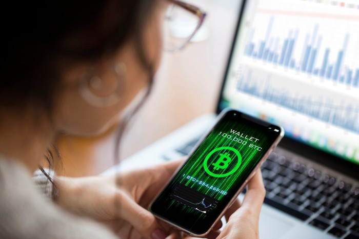 Person using cryptocurrency application on smartphone.