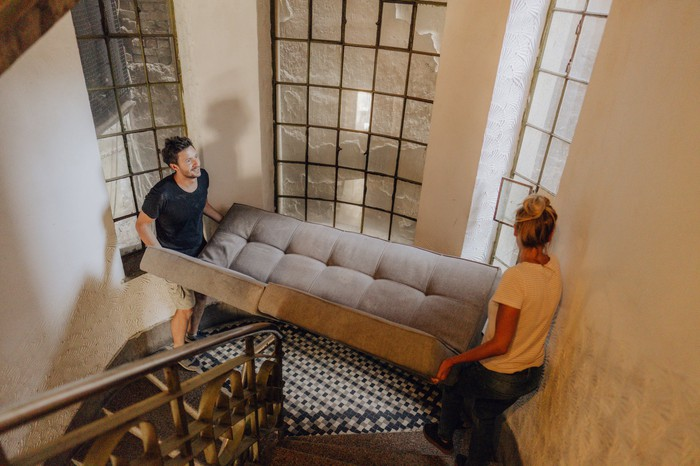 Two people carrying furniture up a staircase.