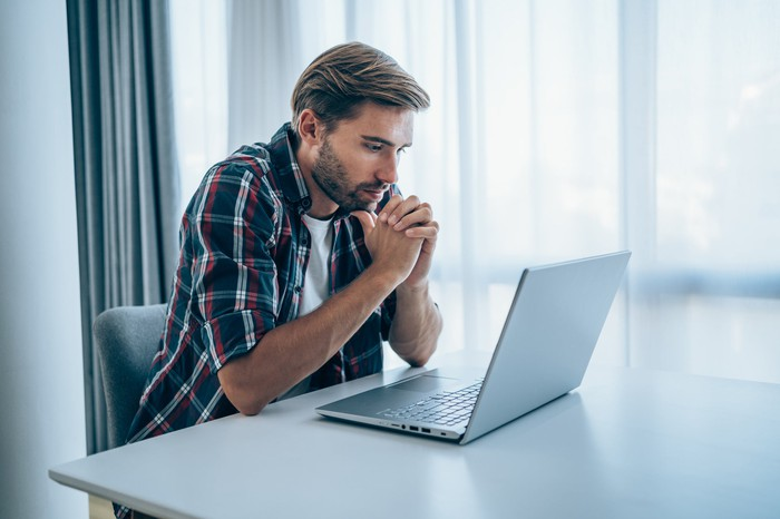 A person sits at a table and looks at a laptop.